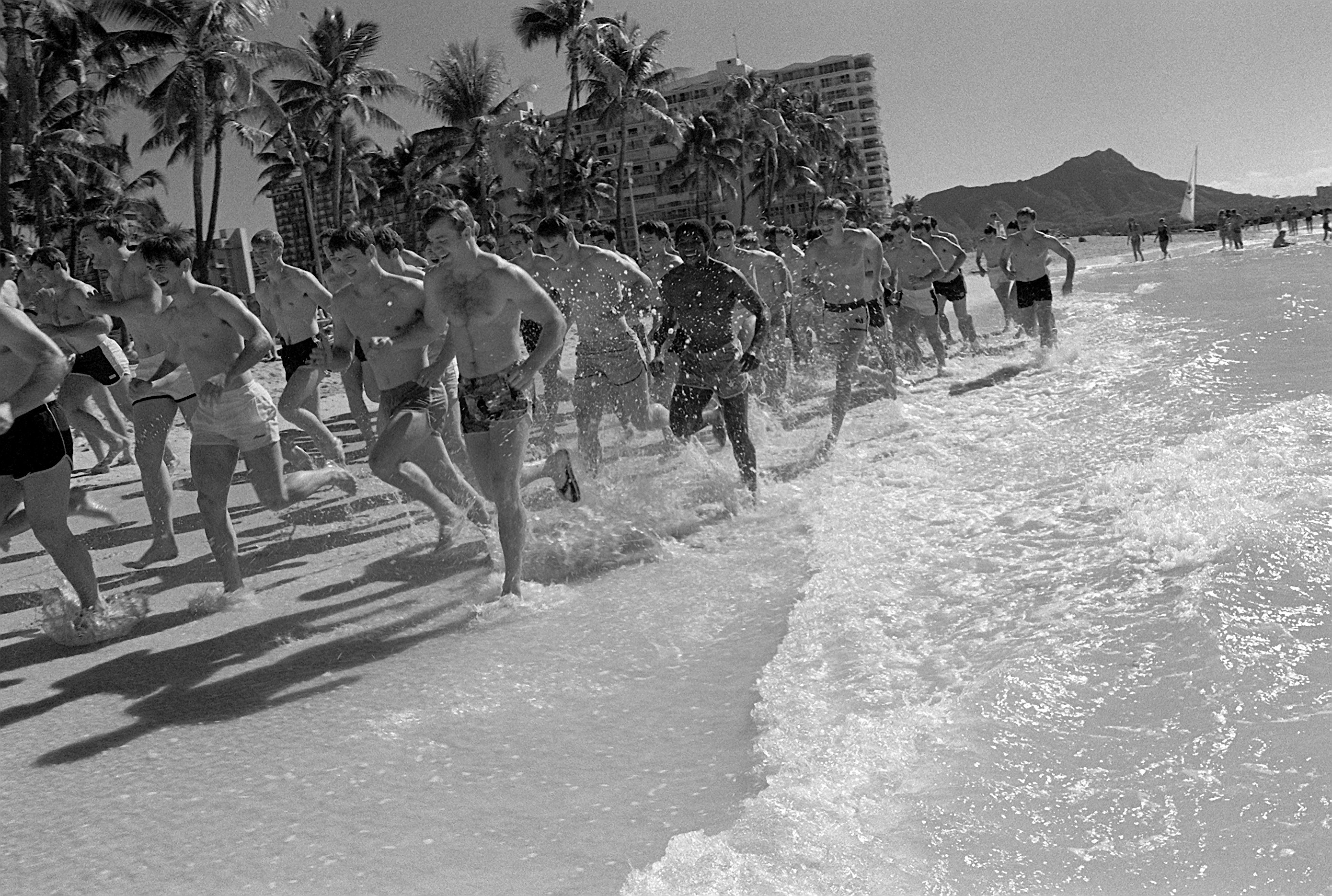 Members of the Air Force Academy football team job on Waikiki Beach before their game with the team from the University of Hawaii / Wikimedia Commons