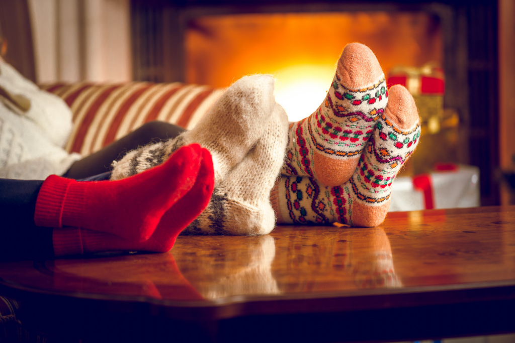 Closeup of family warming feet at fireplace, by kedusource / Flickr